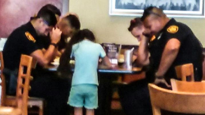 O fetiță îi invită pe polițiști la rugăciune, într-un restaurant